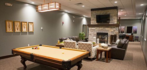 Lounge and billiards table with fireplace and TVs